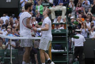 Canada's Denis Shapovalov, right, greets Russia's Karen Khachanov at the end of the men's singles quarterfinals match on day nine of the Wimbledon Tennis Championships in London, Wednesday, July 7, 2021. (AP Photo/Alastair Grant)