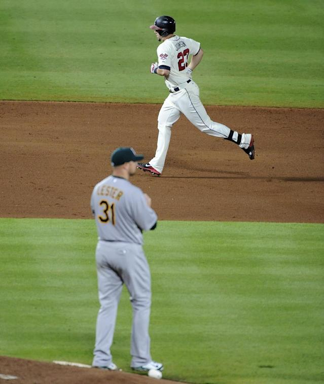 Atlanta Braves' Chris Johnson (23) rounds the bases behind Oakland Athletics starting pitcher Jon Lester (31) after Johnson's solo home run during the seventh inning of a baseball game Sunday, Aug. 17, 2014, in Atlanta. (AP Photo/David Tulis)