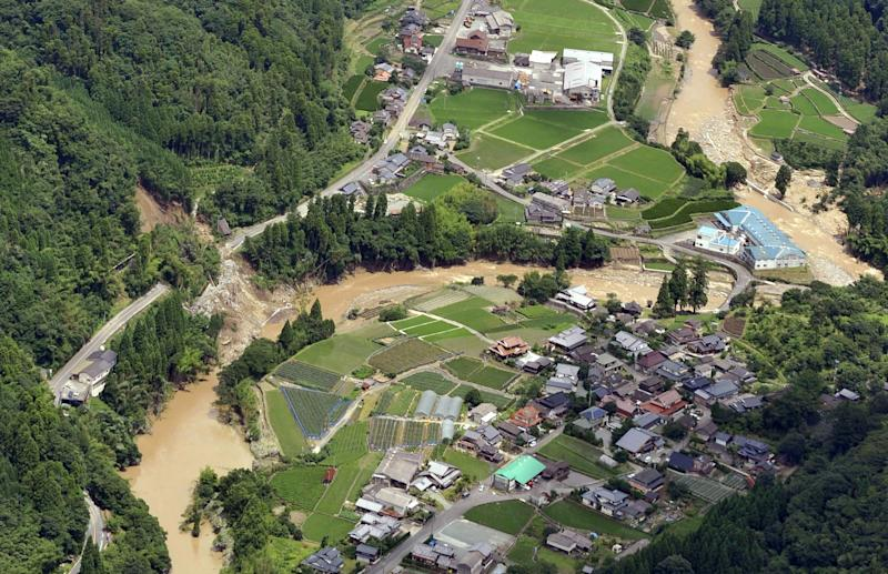 A road, left, is buried in a landslide in Yame, Fukuoka Prefecture, Japan, Sunday, July 15, 2012. Heavy rain triggered flash floods and mudslides in southern Japan this week, killing over two dozens of people. (AP Photo/Kyodo News) JAPAN OUT, MANDATORY CREDIT, NO LICENSING IN JAPAN, CHINA, HONG KONG, SOUTH KOREA AND FRANCE