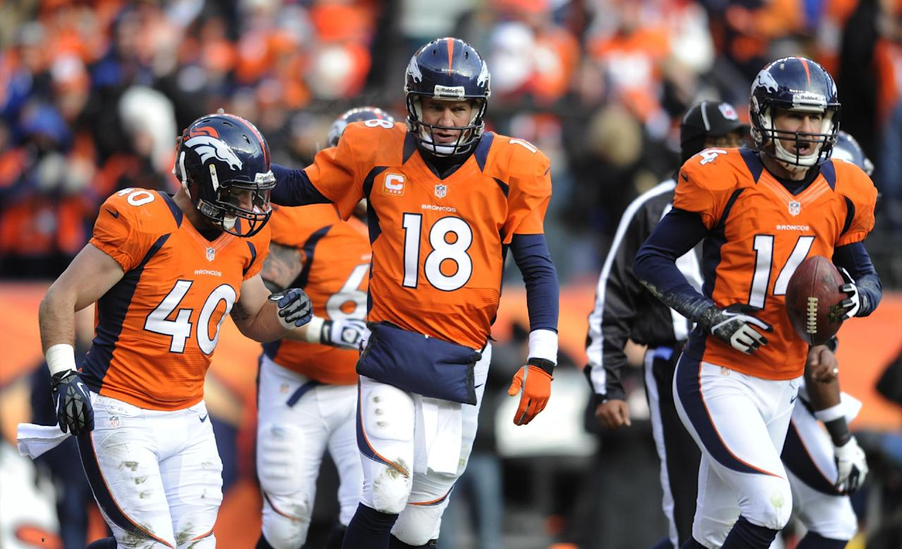 Denver Broncos quarterback Peyton Manning, center, walks off the field with Denver Broncos running back Jacob Hester and wide receiver Brandon Stokley (14) after throwing a touchdown pass to Stokley against the Baltimore Ravens in the first quarter of an AFC divisional playoff NFL football game, Saturday, Jan. 12, 2013, in Denver. (AP Photo/Jack Dempsey)