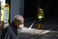 A municipal worker sprays disinfectant on a pavement as a man wearing face mask to prevent the spread of the new coronavirus walks at Ermou Street, Athens' main shopping area, Monday, Sept. 21, 2020. Greece is tightening restrictions in the greater Athens region, stepping up testing and creating quarantine hotels due to an increase in COVID-19 infections after Athenians returned from their summer holidays. (AP Photo/Thanassis Stavrakis)