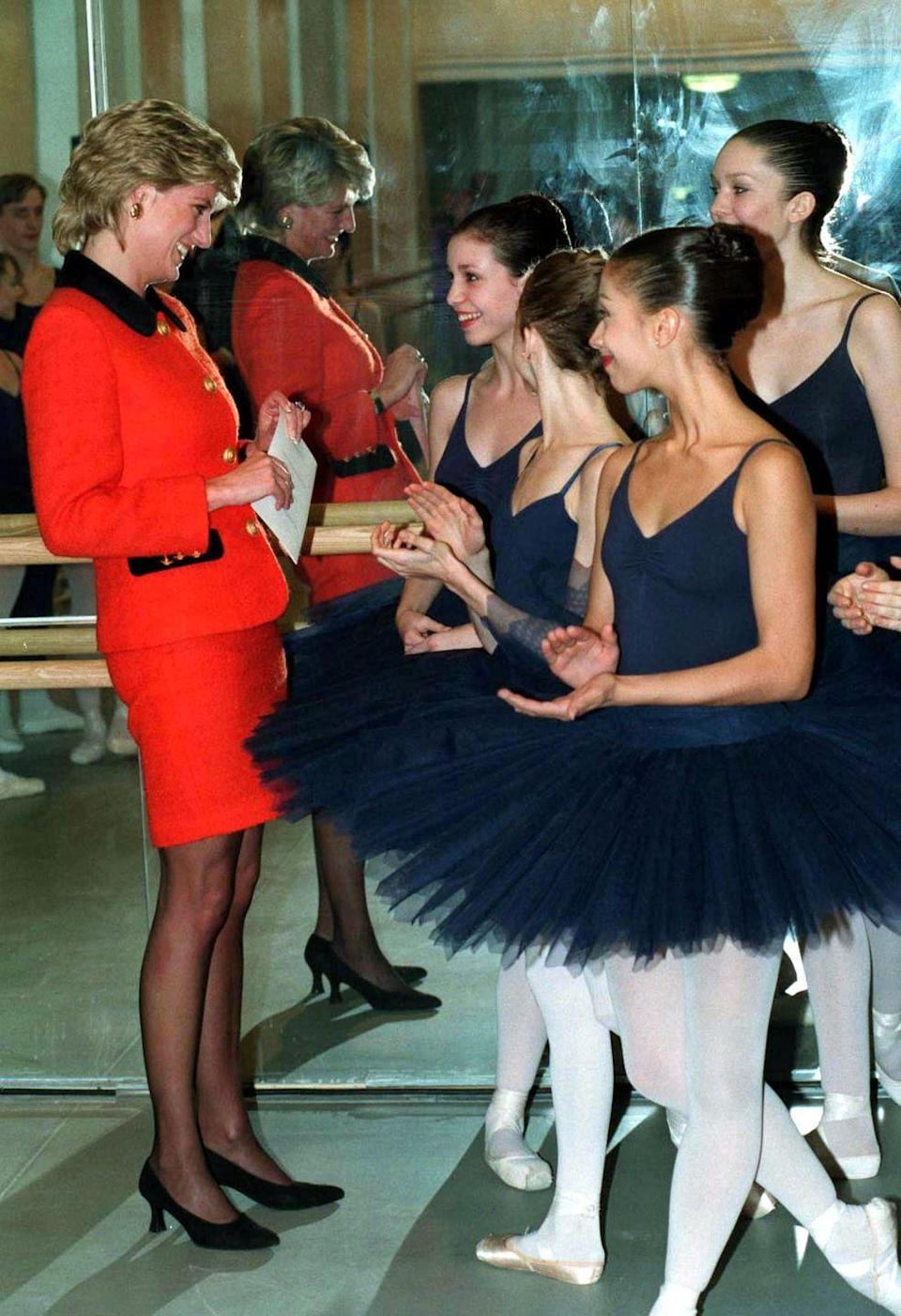 <p>Princess Diana shares a smile with a young dancer while visiting the London headquarters of the English National Ballet in December of 1995.</p>