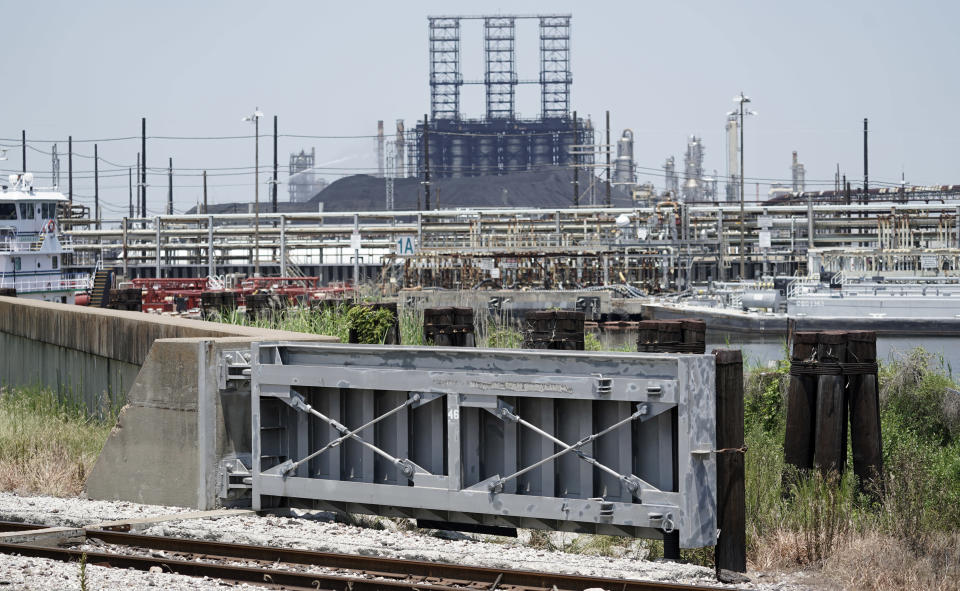 """A flood gate and seawall that will be increased in size, is shown near a refinery Thursday, July 26, 2018, in Port Arthur, Texas. The oil industry wants the government to help protect some of its facilities on the Texas Gulf Coast against the effects of global warming. One proposal involves building a nearly 60-mile """"spine"""" of flood barriers to shield refineries and chemical plants. Many Republicans argue that such projects should be a national priority. But others question whether taxpayers should have to protect refineries in a state where top politicians still dispute whether climate change is real. (AP Photo/David J. Phillip)"""