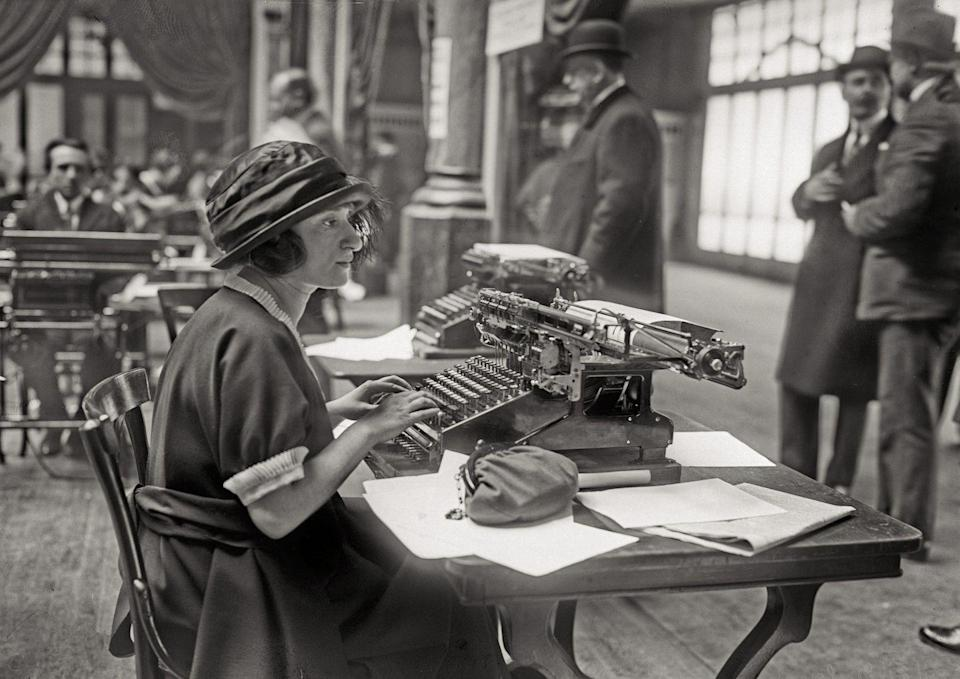 <p>A young woman sitting at a typewriter prepares for a typing exam in Paris, France. </p>