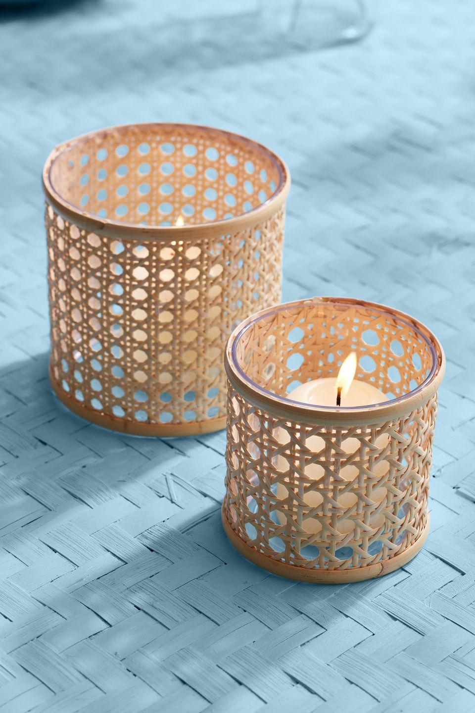 <p>Running down the center of the dining table, these cane webbing covered votive holders add texture to a pretty centerpiece.<strong><br></strong></p><p><strong>To make: </strong>Measure the height and circumference of a glass votive holder. Cut caning to fit around the holder. Spray the back with adhesive spray, such as Super 77; attach to the glass. Cut pieces of flat reed the diameter of the holder, and attach to the top and bottom edges with hot-glue.</p>