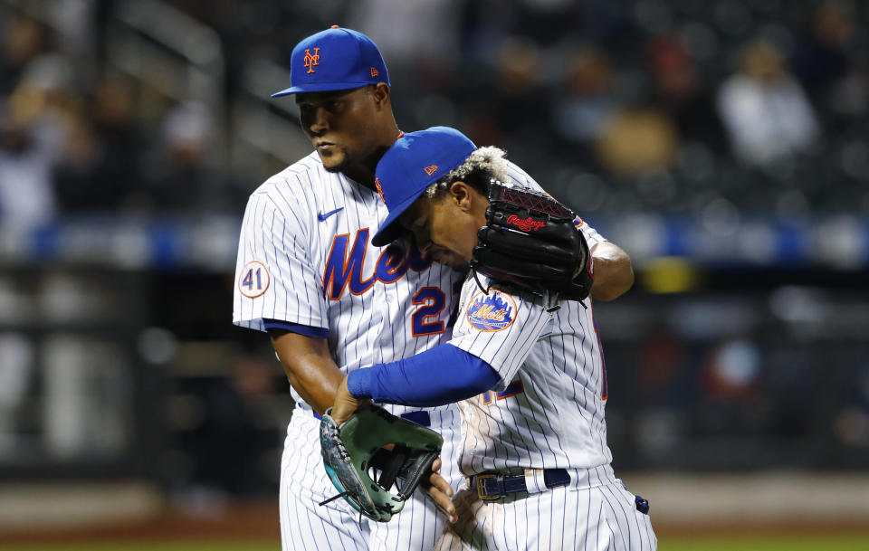 New York Mets relief pitcher Jeurys Familia (27) hugs Francisco Lindor after the top of the seventh inning against the Arizona Diamondbacks in a baseball game Saturday, May 8, 2021, in New York. (AP Photo/Noah K. Murray)