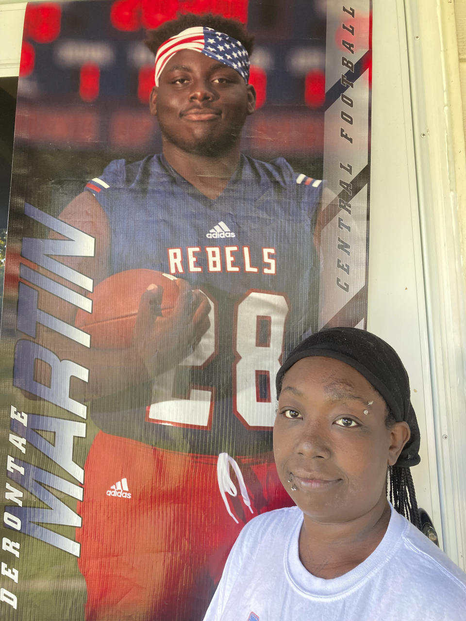 Ericka Lotts stands next to a poster of her son, Derontae Martin, from his high school football playing days, on Friday, Sept. 17, 2021, at her home in Ferguson, Mo. Lotts is frustrated by the pace of the investigation into Martin's death. The 19-year-old died in April at a home in rural Missouri. (AP Photo by Jim Salter)