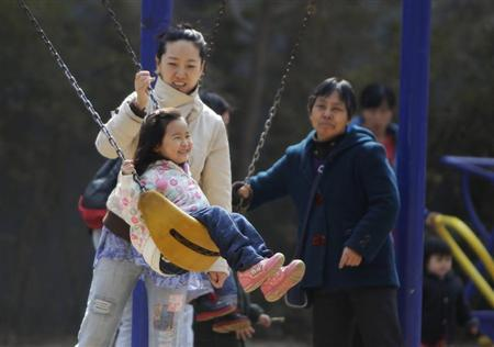 A mother pushes her daughter on a swing in Beijing