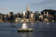 FILE PHOTO: A Star Ferry boat crosses Victoria Harbour in front of a skyline of buildings in Hong Kong