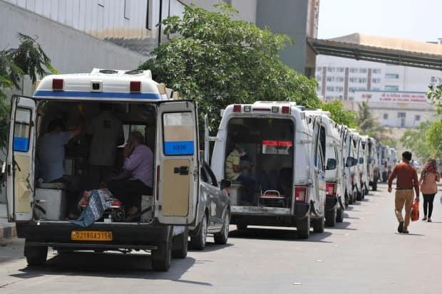 Ambulances carrying COVID-19 patients line up waiting for their turn to be attended at a dedicated COVID-19 government hospital in Ahmedabad, India, on Thursday. (Ajit Solanki/The Associated Press - image credit)