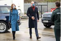 """<p>Prince William and the Duchess of Cambridge spent three days <a href=""""https://www.townandcountrymag.com/society/tradition/a34891776/kate-middleton-prince-william-reindeer-royal-train-tour/"""" rel=""""nofollow noopener"""" target=""""_blank"""" data-ylk=""""slk:aboard the royal train"""" class=""""link rapid-noclick-resp"""">aboard the royal train</a>, touring Scotland, England, and Wales. On the tour's second day, Kate chose a tailored blue Catherine Walker coat. She accessorized with black leather gloves, heeled suede boots, and a blue floral mask. </p>"""