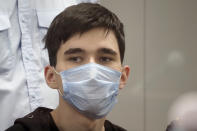 """Ilnaz Galyaviyev, wearing a face mask to protect against coronavirus, sits in a courtroom in Kazan, Russia, Wednesday, May 12, 2021. Russian officials say Galyaviyev attacked a school in the city of Kazan and Russian officials say several people have been killed. Russian media said the gunman was a former student at the school who called himself """"a god"""" on his account on the messaging app Telegram and promised to """"kill a large amount of biomass"""" on the morning of the shooting. Authorities also say over 20 others have been hospitalised with wounds. (AP Photo/Dmitri Lovetsky)"""