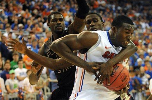 Florida's Patric Young, right, gets hung up as he tries to get around Florida State's Okaro White, center, during the first half of an NCAA college basketball game in Gainesville, Fla., Thursday, Dec. 22, 2011. (AP Photo/ Phil Sandlin)