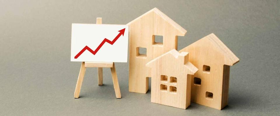 three wooden houses and a red arrow up on the sign.  Increase in real estate value.  High build rates, high liquidity.  Supply and demand.  Rising housing prices, building maintenance.