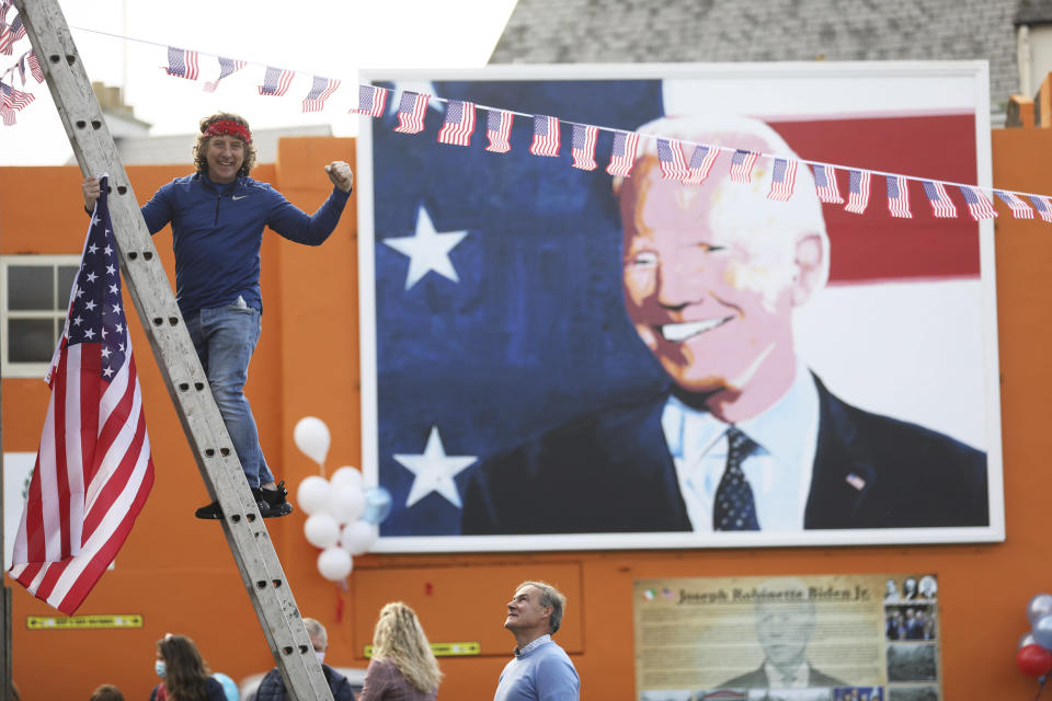 A man puts a US flag up in the town of Ballina, the ancestral home of President elect Joe Biden, in North West of Ireland, Saturday, Nov. 7, 2020. Biden was elected Saturday as the 46th president of the United States, defeating President Donald Trump in an election that played out against the backdrop of a pandemic, its economic fallout and a national reckoning on racism. (AP Photo/Peter Morrison)