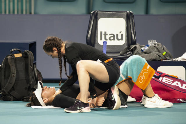 Bianca Andreescu, of Canada, gets checked out by a trainer during her match against Angelique Kerber, of Germany, during the Miami Open tennis tournament Sunday, March 24, 2019, in Miami Gardens, Fla. (AP Photo/Gaston De Cardenas)