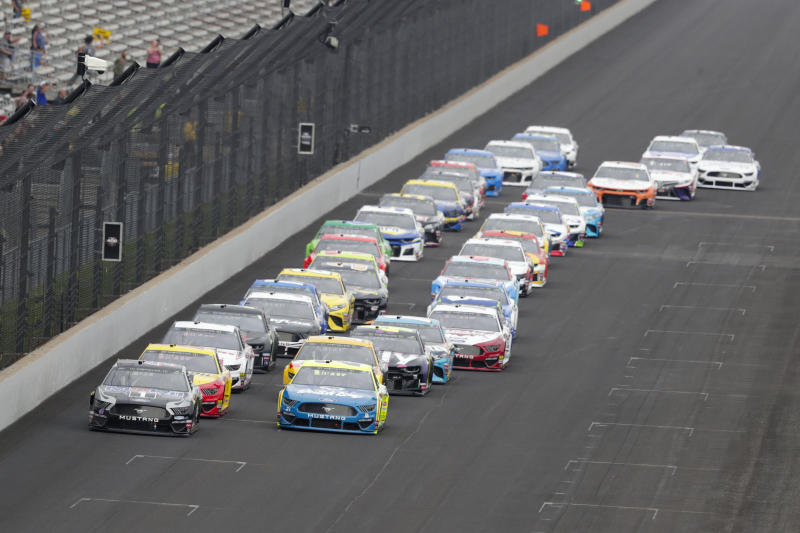 Kevin Harvick, left and Paul Menard lead the field into the first turn on the start of the NASCAR Brickyard 400 auto race at Indianapolis Motor Speedway, Sunday, Sept. 8, 2019, in Indianapolis. (AP Photo/Michael Conroy)
