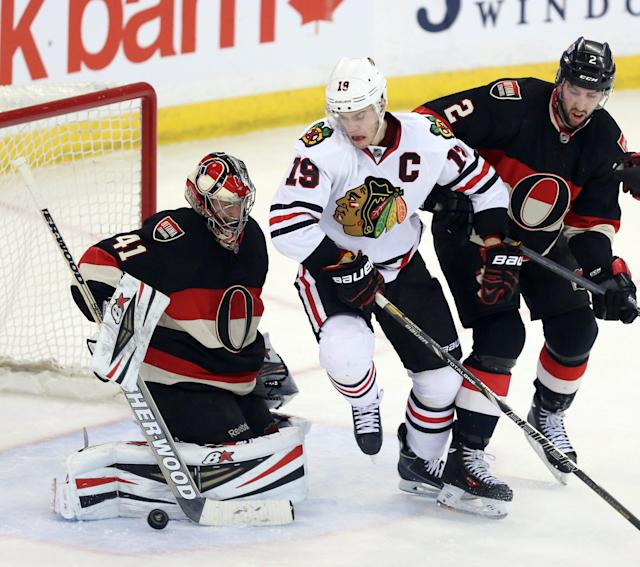 Ottawa Senators goaltender Craig Anderson (41) clears the puck as teammate Jared Cowen (2) and Chicago Blackhawks' Jonathan Toews (19) battle in front of the net during second-period NHL hockey game action in Ottawa, Ontario, Friday, March 28, 2014. (AP Photo/The Canadian Press, Fred Chartrand)