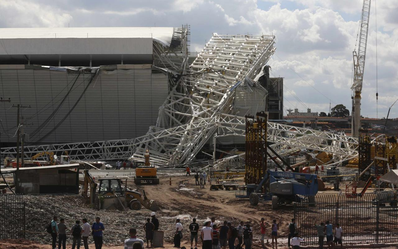 """Workers stand near a crane that collapsed on the site of the Arena Sao Paulo stadium, known as """"Itaquerao"""", which will host the opening soccer match of the 2014 World Cup, in Sao Paulo November 27, 2013. A crane collapsed on Wednesday at the construction site of a future World Cup soccer stadium in Sao Paulo, Brazil, killing at least three people and causing damage to the structure, local media said. REUTERS/Nacho Doce (BRAZIL - Tags: SPORT SOCCER WORLD CUP TPX IMAGES OF THE DAY)"""