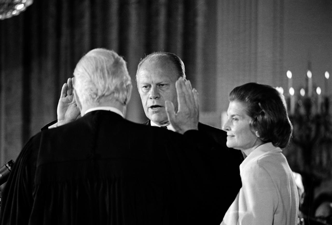 Gerald R. Ford takes the oath of office as the 38th president of the United States as his wife, Betty, right, stands at his side in the East Room of the White House in Washington, D.C., Aug. 4. 1974.  Administering the oath is Chief Justice of the United States Warren Burger.  Ford is sworn in following the resignation of Richard M. Nixon as chief executive.  (AP Photo)