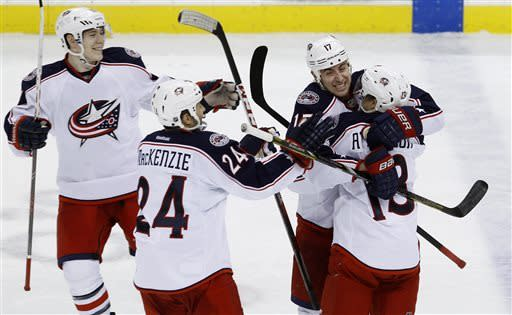 Columbus Blue Jackets center Brandon Dubinsky (17) hugs right wing Cam Atkinson (13) as teammates Derek MacKenzie (24) and Matt Calvert, left, join the celebration after the Blue Jackets defeated the Wild 3-2 in a shootout of an NHL hockey game in St. Paul, Minn., Saturday, April 13, 2013. (AP Photo/Ann Heisenfelt)