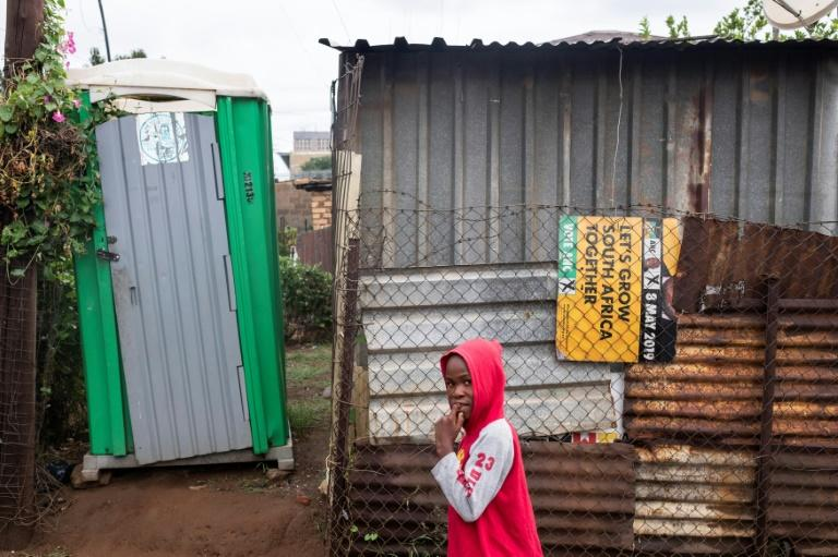 A child walks past a shack with a makeshift toilet outside and an ANC poster for May 8 elections seen as a key test of the party's ability to deliver on its post-apartheid promises