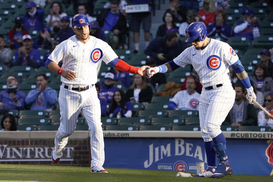 Chicago Cubs' Willson Contreras, left, is greeted by Javier Baez, right, after scoring against the Washington Nationals during the first inning of a baseball game, Monday, May, 17, 2021, in Chicago. (AP Photo/David Banks)