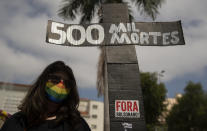 """A woman, wearing a protective face mask, holds a sign in the shape of a cross with a message that reads in Portuguese;""""500 k deaths"""", during a protest against Brazilian President Jair Bolsonaro and his handling of the pandemic and economic policies protesters say harm the interests of the poor and working class, in Cuiaba, Brazil, Saturday, June 19, 2021. Brazil is approaching an official COVID-19 death toll of 500,000 — second-highest in the world. (AP Photo/Andre Penner)"""