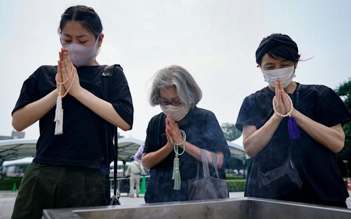 Women pray in front of a cenotaph for the victims of the bombing at Peace Memorial Park in Hiroshima - DAI KUROKAWA/EPA-EFE/Shutterstock /Shutterstock