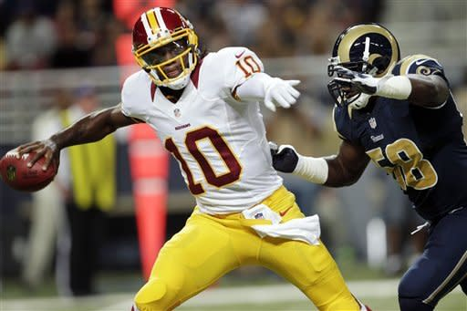 Washington Redskins quarterback Robert Griffin III (10) tries to throw under pressure from St. Louis Rams linebacker Jo-Lonn Dunbar during the first quarter of an NFL football game, Sunday, Sept. 16, 2012, in St. Louis. (AP Photo/Tom Gannam)