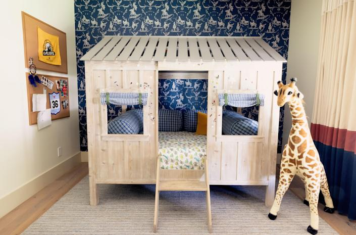 Shepherd sleeps in an RH Kids Cabin Bed set against blue cowboy-print wallpaper from Walnut. His curtains were custom made of dyed canvas by Older Brother.