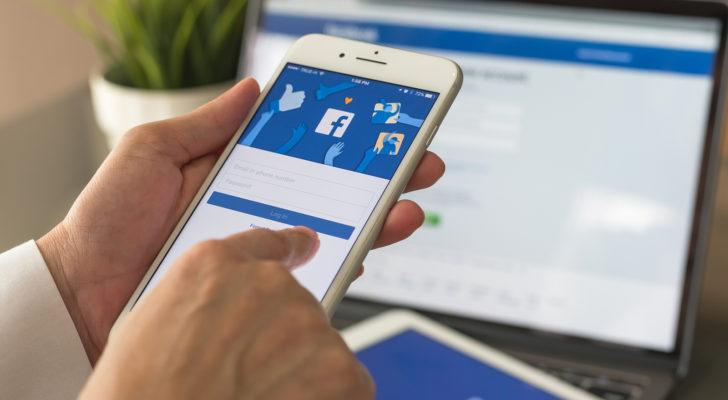 image of person using a Facebook (FB) app on their mobile phone with Facebook also open on an online browser in the background