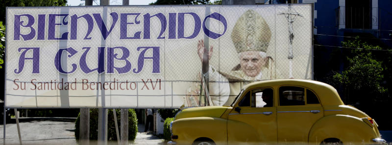 A vintage car drives past a billboard welcoming Pope Benedict XVI, just days before his arrival, in Havana, Cuba, Wednesday March 21, 2012. Pope Benedict XVI's trip to Latin America takes him to the region's most Catholic country; Mexico, and then Cuba, where churches are mostly empty and until the 1990s, believers were barred from the Communist Party. (AP Photo/Javier Galeano)