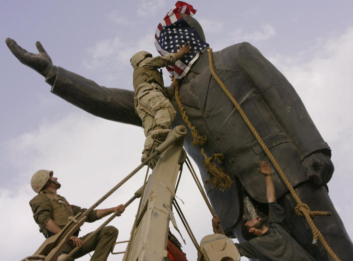 FILE - In this April 9, 2003, file photo, an Iraqi man, bottom right, watches Cpl. Edward Chin of the 3rd Battalion, 4th Marines Regiment, cover the face of a statue of Saddam Hussein with an American flag before toppling the statue in downtown Baghdad, Iraq. (AP Photo/Jerome Delay, File)