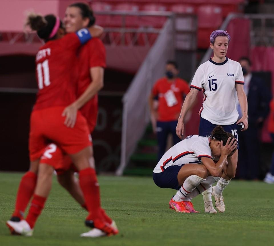 A despondent Team USA forward Carli Lloyd (10) crouches on the field as teammate Megan Rapinoe approaches to console her.