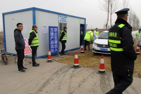 Police officers and workers in protective suits are seen at a checkpoint on a road leading to a farm owned by Hebei Dawu Group where African swine fever was detected, in Xushui district of Baoding, Hebei province, China February 26, 2019. REUTERS/Hallie Gu