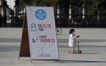 A banner showing mandatory mask wearing and social distancing as a precaution against the coronavirus, is seen at a park in Seoul, South Korea, Saturday, Oct. 24, 2020. (AP Photo/Lee Jin-man)