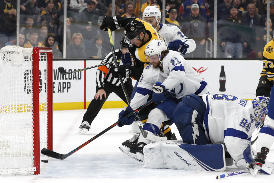 Tampa Bay Lightning's Brayden Point (21) reaches but cannot keep the puck from crossing the line for a goal by Boston Bruins' Sean Kuraly (52) during the second period of an NHL hockey game Saturday, March 7, 2020, in Boston. (AP Photo/Winslow Townson)