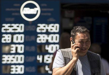 Man talks on his mobile phone as he walks past board showing currency exchange rates in Almaty
