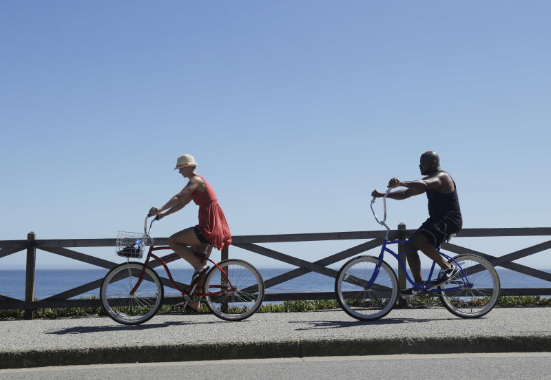 A couple bike along the ocean on a hot day in Santa Cruz, Calif., Thursday, June 27, 2013. (AP Photo/Marcio Jose Sanchez)