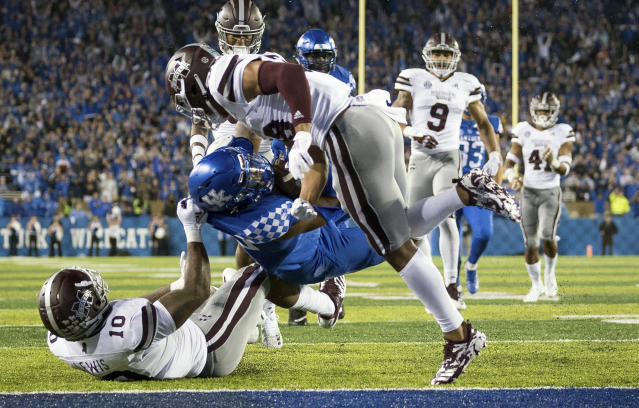Kentucky running back Benny Snell Jr. (26) leaps into the end zone between several Mississippi State defenders for a touchdown during the second half of an NCAA college football game in Lexington, Ky., Saturday, Sept. 22, 2018. (AP Photo/Bryan Woolston)