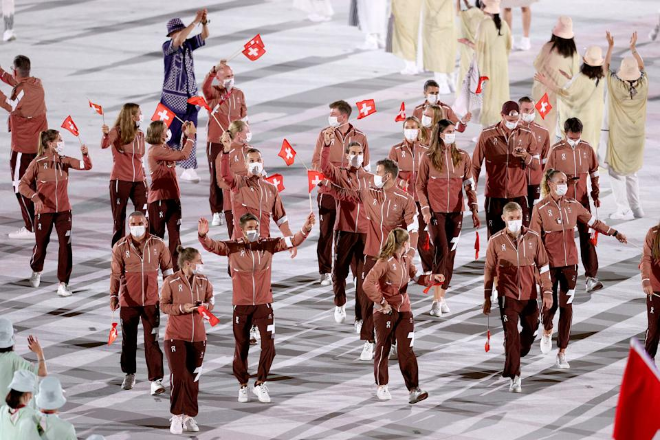 <p>TOKYO, JAPAN - JULY 23: Flag bearers Mujinga Kambundji and Max Heinzer of Team Switzerland leads their team out during the Opening Ceremony of the Tokyo 2020 Olympic Games at Olympic Stadium on July 23, 2021 in Tokyo, Japan. (Photo by Patrick Smith/Getty Images)</p>