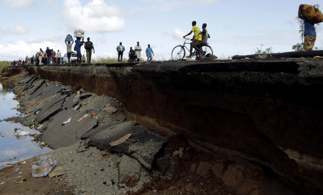 Pedestrians walk on the edge of a collapsed bridge in Nhamatanda, about 100km west of Beira, Thursday, March 21, 2019. Some hundreds are dead, many more still missing and thousands at risk from massive flooding across the region including Mozambique, Malawi and Zimbabwe caused by Cyclone Idai. (AP Photo/Themba Hadebe)