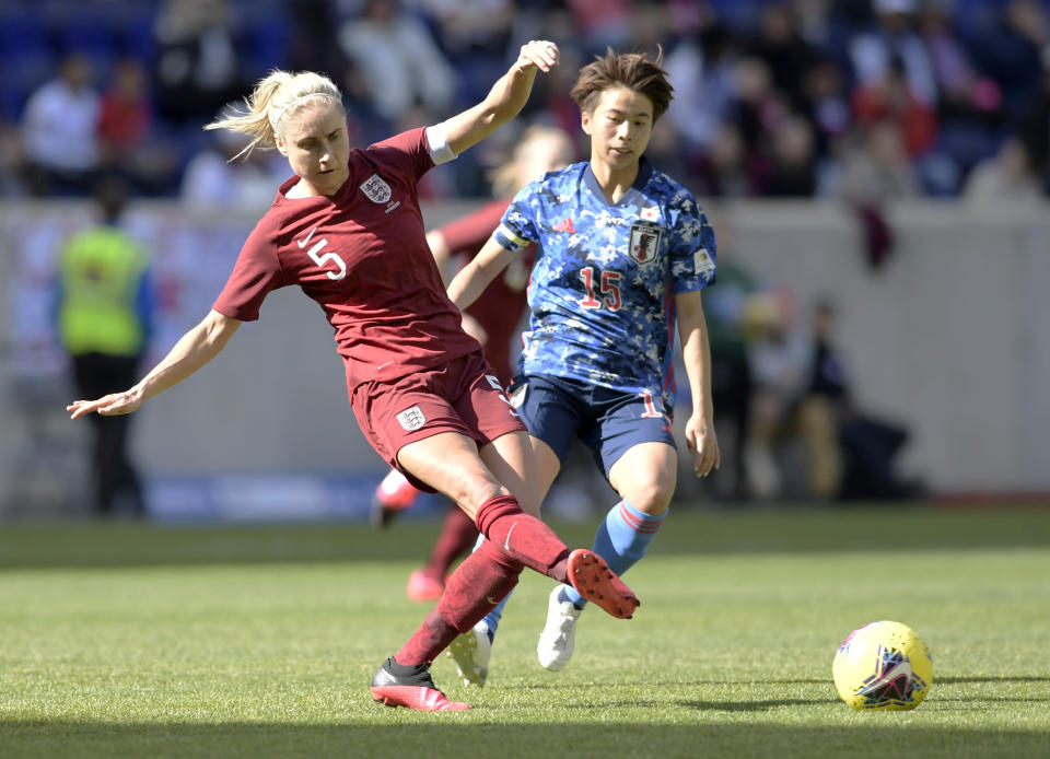 England defender Steph Houghton (5) passes the ball as Japan forward Mina Tanaka (15) looks on during the first half of a SheBelieves Cup soccer match Sunday, March 8, 2020, in Harrison, N.J. (AP Photo/Bill Kostroun)
