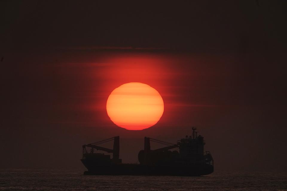 The sun rises through the mist over a BBC Fuji Cargo Ship anchored just of the north east coast at Tynemouth. Picture date: Tuesday July 16, 2019. A partial lunar eclipse is set to be visible across parts of the UK on Tuesday, if clear weather and conditions hold up. See PA story WEATHER Sunrise. Photo credit should read: Owen Humphreys/PA Wire