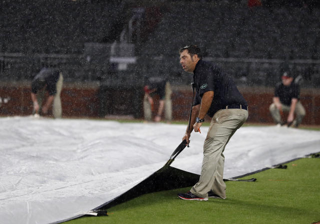 Members of the Atlanta Braves ground crew work to cover the infield during a rain delay in seventh inning of a baseball game between the Braves and Pittsburgh Pirates on Wednesday, June 12, 2019, in Atlanta. (AP Photo/John Bazemore)