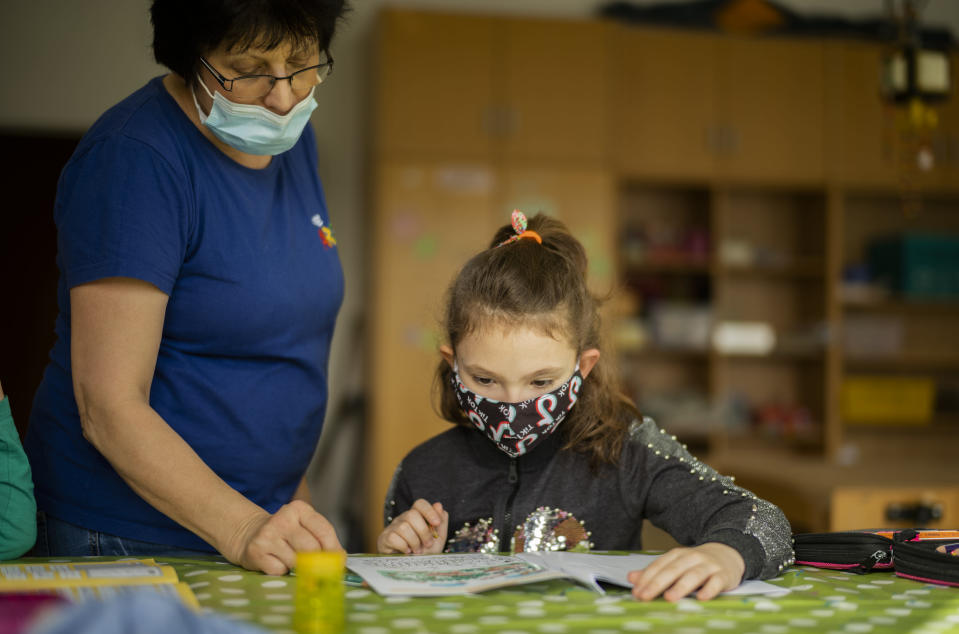 Nine-year-old girl Pauline receives assistance for her schoolwork by a social worker at the Arche, or Ark, an organization that supports children, youth and families in the Hellersdorf neighbourhood, on the eastern outskirts of Berlin, Germany, Tuesday, Feb. 23, 2021. Since the outbreak of the coronavirus pandemic, the Arche has had to reduce their real face-to-face assistance or traditional classroom schooling as an offer for children, mainly from underprivileged families, drastically. Some kids are still allowed to come over in person, but only once every two weeks. (AP Photo/Markus Schreiber)