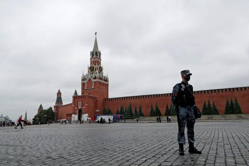 A law enforcement officer stands guard in Red Square after an opposition activist reportedly simulated shooting himself in the head in a political protest, in Moscow