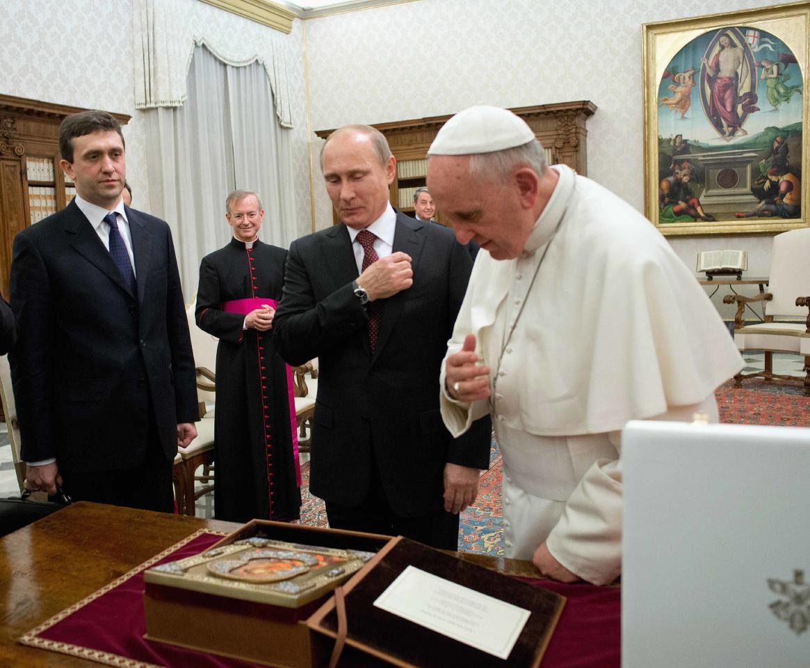 Pope Francis (R) exchanges gifts with Russia's President Vladimir Putin during a private audience at the Vatican, November 25, 2013. REUTERS/Osservatore Romano (VATICAN - Tags: RELIGION POLITICS) ATTENTION EDITORS - THIS IMAGE WAS PROVIDED BY A THIRD PARTY. FOR EDITORIAL USE ONLY. NOT FOR SALE FOR MARKETING OR ADVERTISING CAMPAIGNS. THIS PICTURE IS DISTRIBUTED EXACTLY AS RECEIVED BY REUTERS, AS A SERVICE TO CLIENTS. NO SALES. NO ARCHIVES