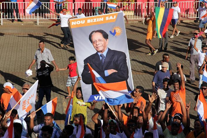 Supporters of the centre-right coalition Alliance Lepep hold a poster of the coalition's leader, former president Anerood Jugnauth in Riviere du Rempart, Mauritius, December 11, 2014 (AFP Photo/Nicholas Larche)